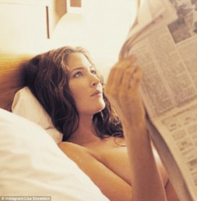 Lisa Snowdon is reading a newspaper on the bed
