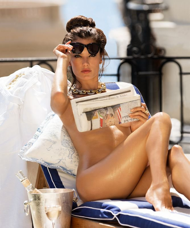 Alessandra Ambrosio is holding a newspaper
