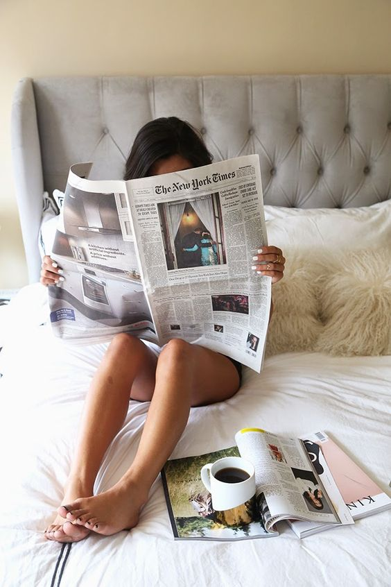 A girl is reading a newspaper