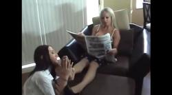 A teen girl is licking her foot while she is reading the newspaper